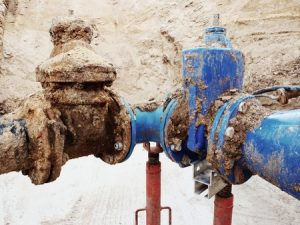 62796805 - old big drink water pipes joined with new blue gate valves and reduction joint members. finished repaired piping waiting for covering by clay. extreme kind of corrosion, metal corroded texture.